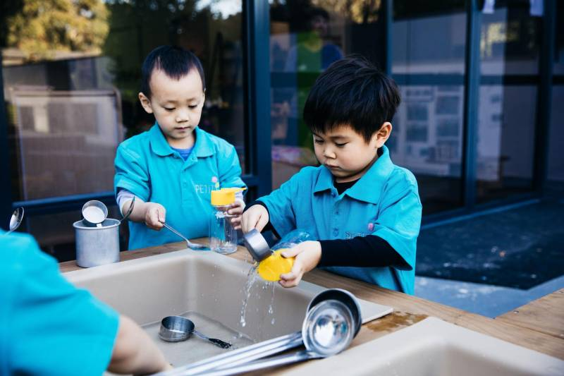 Children fill bottles with water for a science experiment for preschoolers