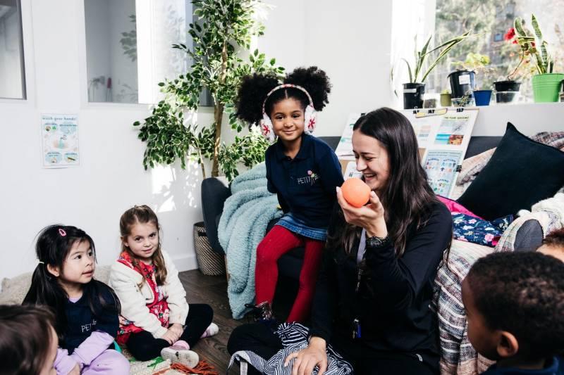 Children sit around preschool Educator holding an orange for a preschool science experiment.