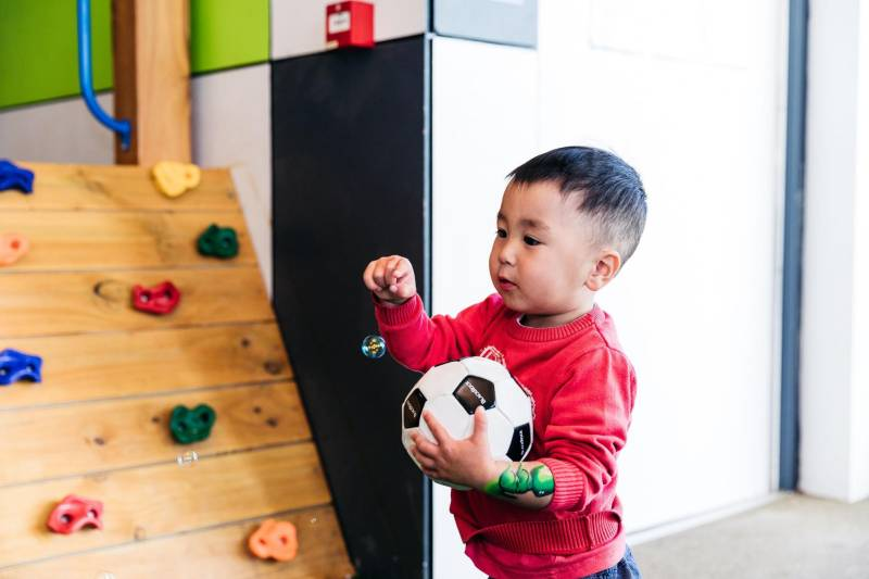 Boy with ball plays with floating bubble, a push and pull preschool science activity.