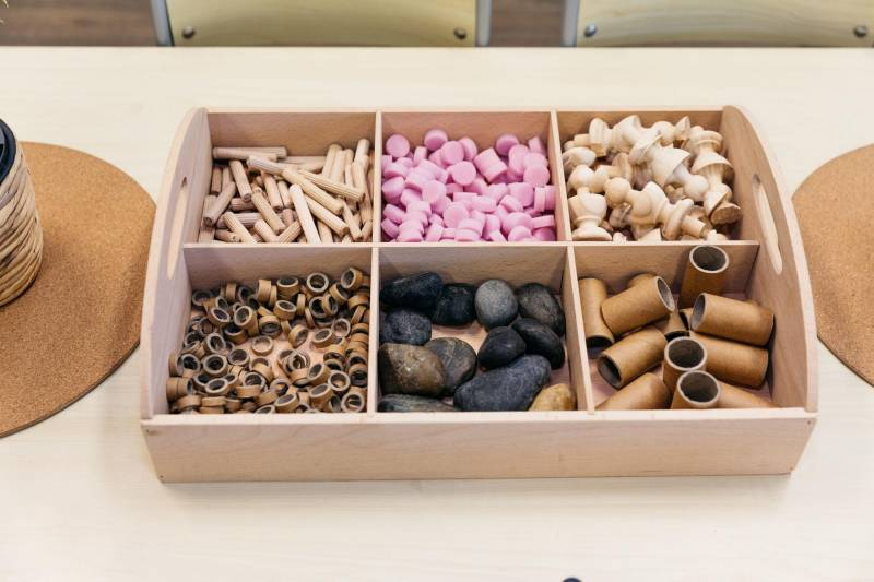 Loose parts in a wooden container enhance sensory play for toddlers.