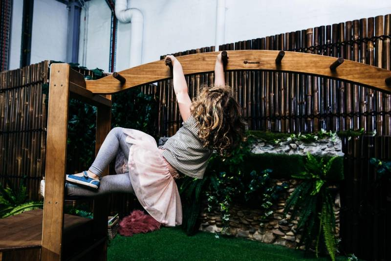 Child plays on monkey bars. Indoor play places are some of the best kids birthday party venues.
