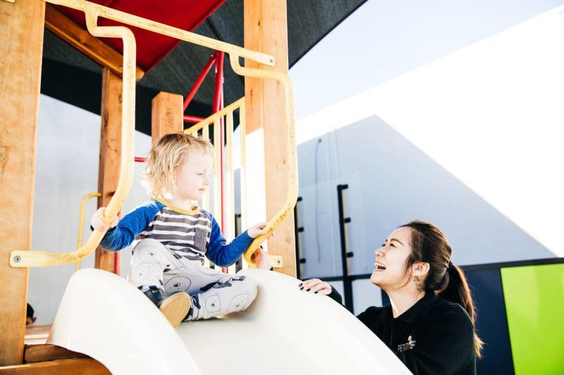 Child sits at the top of the slide in an outdoor area with swings, ideal places for children's birthday parties.
