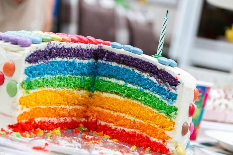 Layered rainbow cake part of a themed birthday party idea.