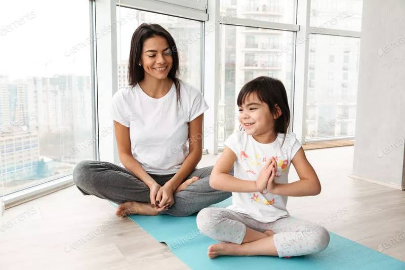 Mum sits on a yoga mat with daughter and inspires children's yoga.