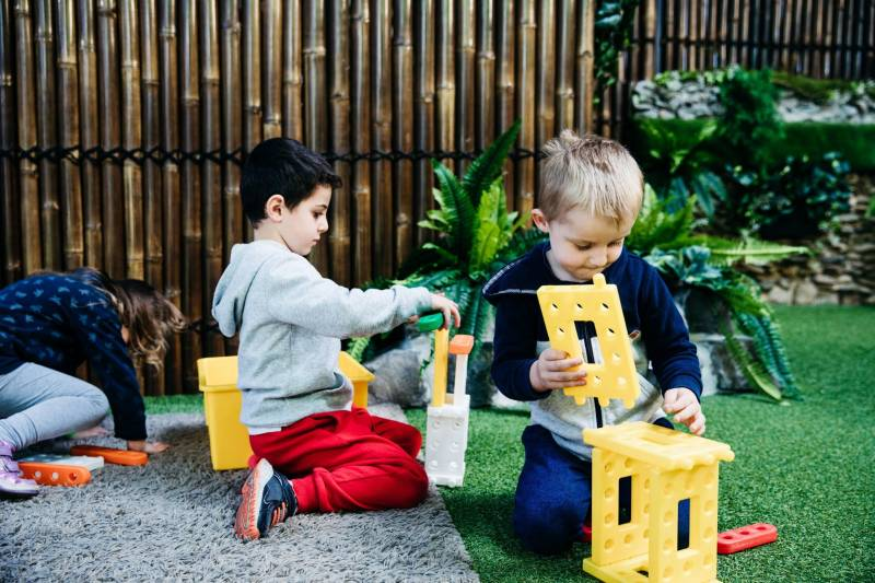 Children play with connector blocks, a fine motor skill example.