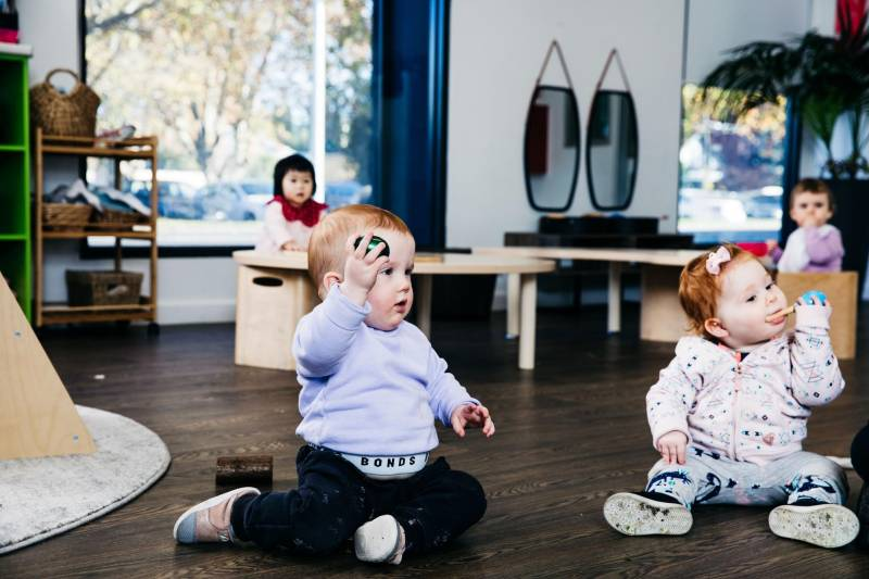 Babies hold and rattle musical shakers for fine motor skill development.