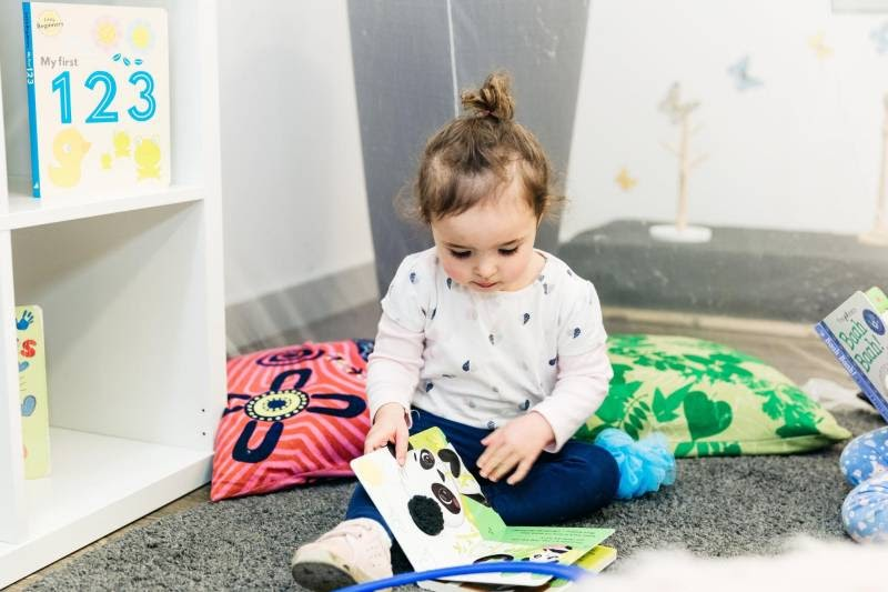 Child reads a book at Petit Early Learning Journey Forest Hill's centre. Kids yoga books build confidence