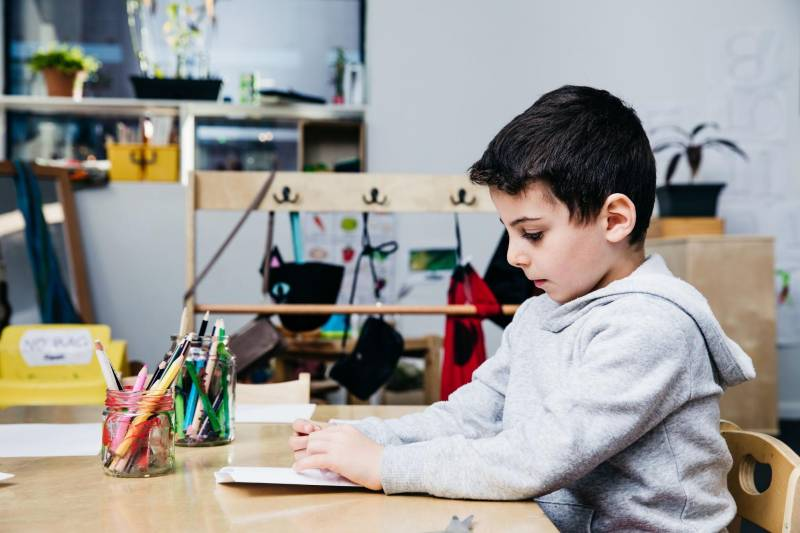 Child sits at desk facing recycled pencil caddies made from glass jars a craft idea for kids with waste material.