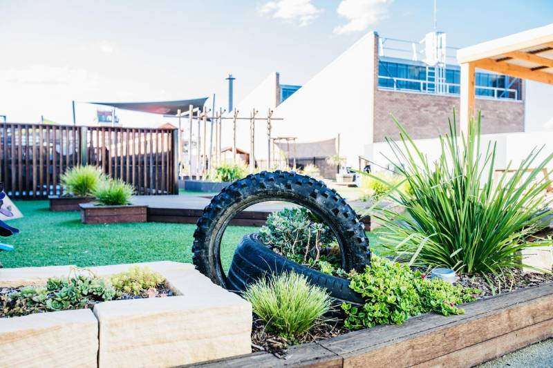 Childcare outdoor play area showing recycled tyres, ideal spaces for recycling activities for preschoolers.