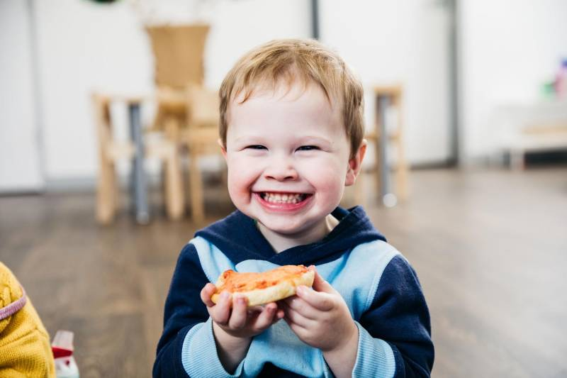 Child grins showing a fine set of baby teeth while eating. Curbing hunger can reduce toddler biting.