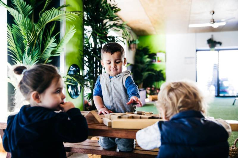 Child reaches for a toy on a table with other children. Wanting toys others have can cause children's biting behaviour.