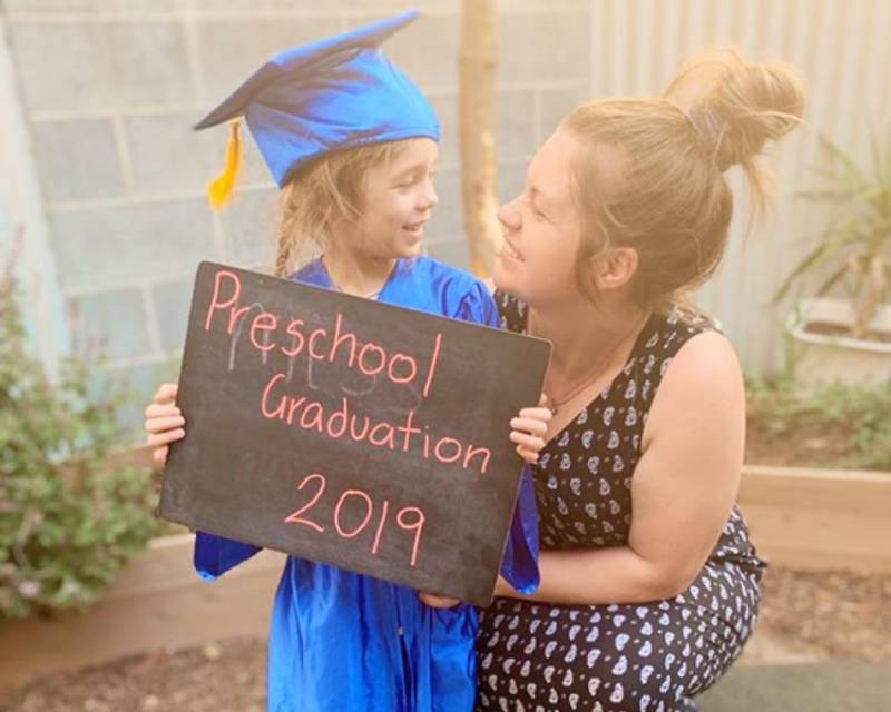 Child with mum holding preschool graduation sign supporting children's transitions to schools