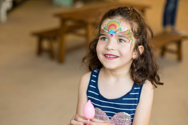 Child learning colours with face painting.