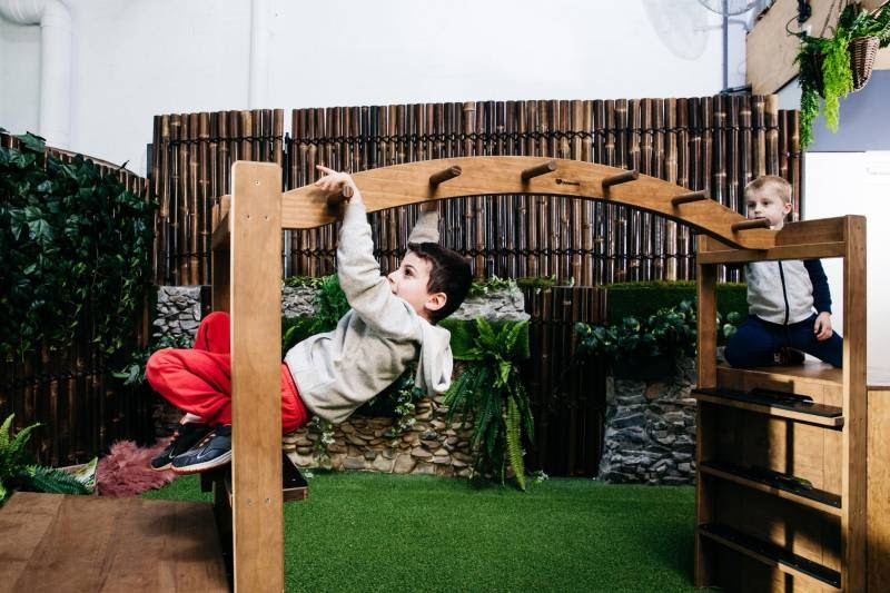 Child learns to swing on monkey bars a gross motor skill activity.