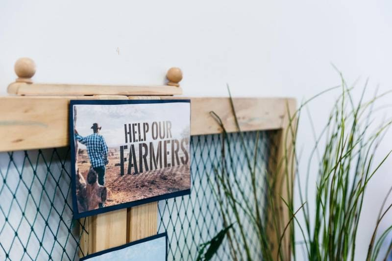 "Sign ""Help our farmers"" helps us to reflect on what work-life balance is."